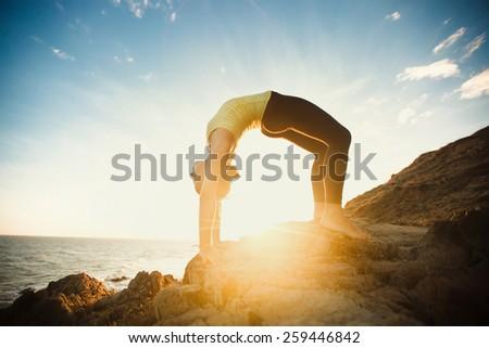 girl is doing yoga, standing in bridge pose ( Setu Bandhasana ) on rocks by the sea with sunset on background - stock photo