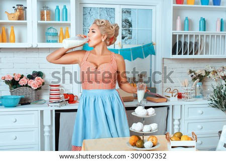 Girl is drinking from a glass of milk. She is in the kitchen. - stock photo
