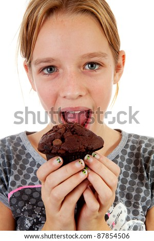 Girl is eating big chocolate cupcake over white background