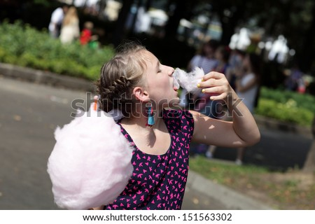 Girl is eating cotton candy in the park - stock photo