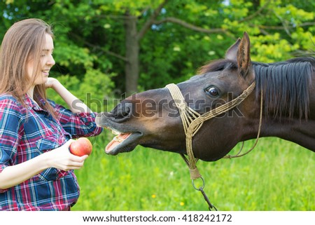 Girl is feeding her horse pet with apple - stock photo