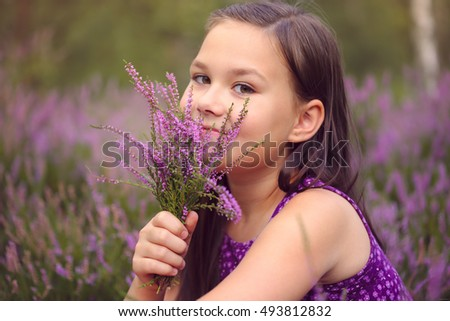 Girl is holding bunch of heather flowers, outdoor shoot