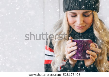 girl is in winter by snow and holding a mug of hot tea. natural light, light background