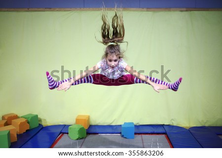 Girl is jumping high in striped tights on the big trampoline. - stock photo