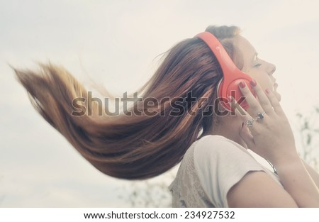 Girl is listen to the music on headphones  - stock photo