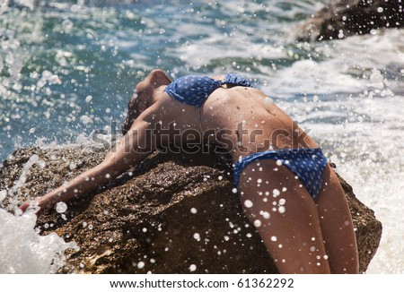 Girl is lying on stone in sea