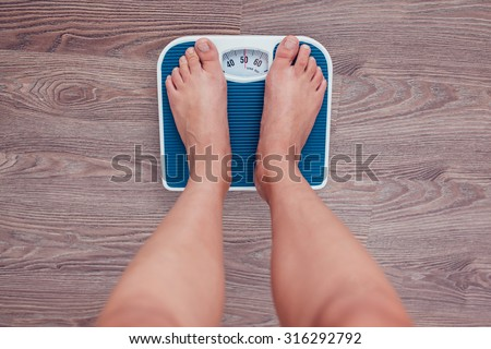 Girl is measuring her weight on the scales. - stock photo