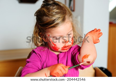 girl is painting her self with watercolors - stock photo