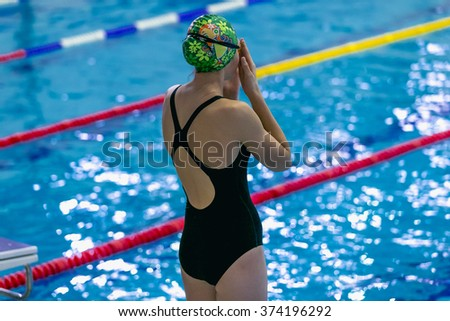 girl is preparing for swimming in stands on side of pool - stock photo