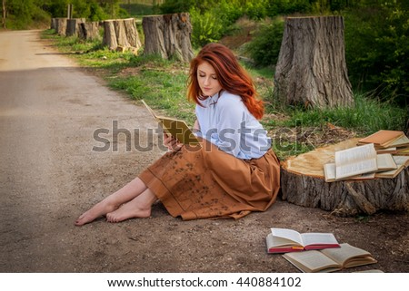 girl is reading a book at alley of felled trees - stock photo