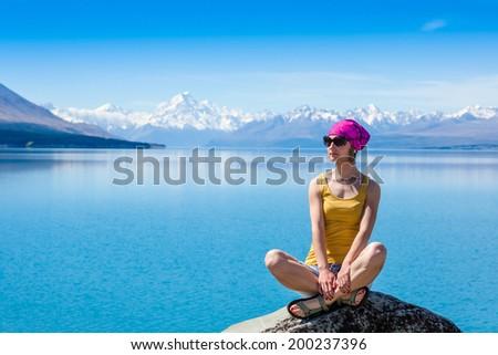 Girl is siting on the rock and enjoying the view. New Zeraland. Tekapo lake  - stock photo
