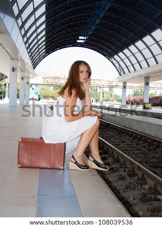 girl is sitting on a suitcase waiting for the train - stock photo