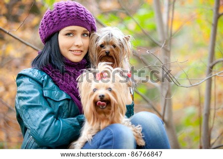 girl is sitting with two small dogs