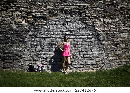 girl is standing near the brick wall - stock photo