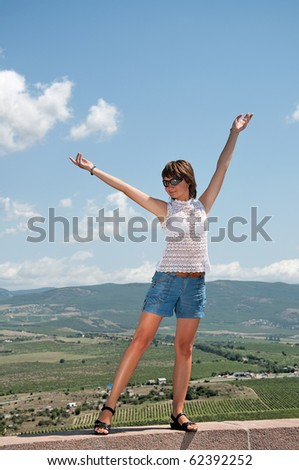 girl is standing with hands up against the background of beautiful scenery - stock photo