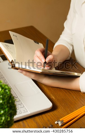Girl is writing something in her notebook from laptop at the table - stock photo