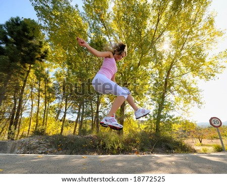 girl jogging/jumping on a road - stock photo
