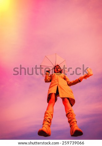 girl jumped with umbrella against the sky - stock photo