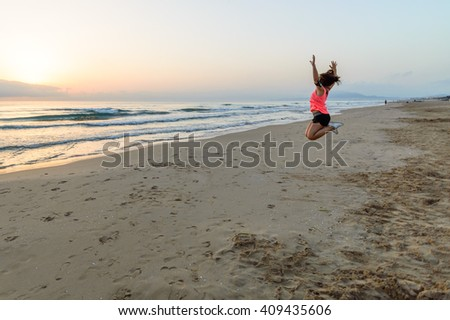 Girl jumping alone at the beach at dawn after running with open arms. Rear view against nature background