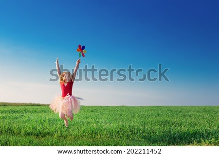 girl jumping and  holding a toy flower