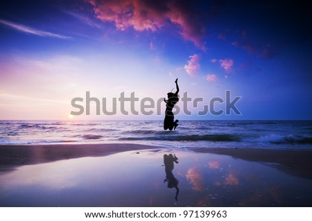 Girl jumping for joy on the sunset beach