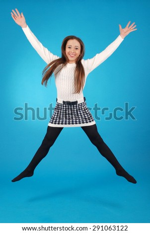 Girl jumping isolated on blue studio background.