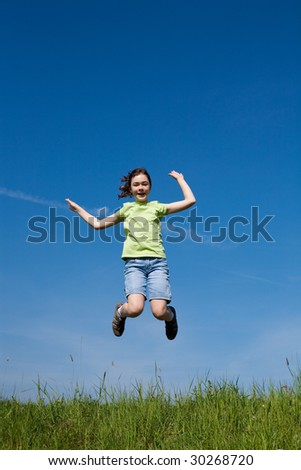 Girl jumping on green meadow against blue sky