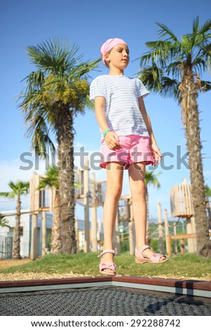Girl jumping on the grid on the playground - stock photo