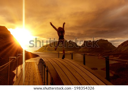 girl jumping on the mountains  background   - stock photo