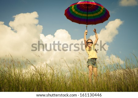 Girl jumping on the road with an umbrella in his hand - stock photo