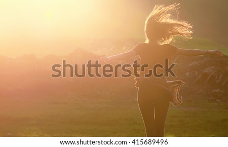 Girl  jumping up in a beautiful sunset setting - stock photo