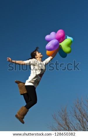 girl jumping with a multicolored heart shape balloons on the background of the sky - stock photo