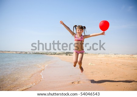 Girl jumping with balloon on the beach - stock photo