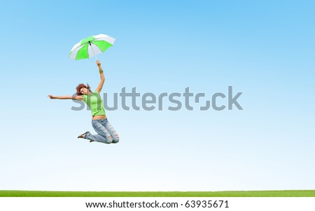 girl jumping with umbrella - stock photo