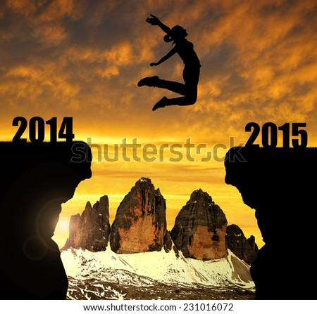Girl jumps to the New Year 2015 in the background Tre cime di Lavaredo, Dolomite Alps, Italy  - stock photo