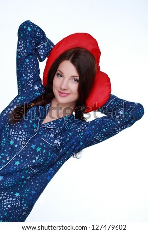 Girl keeps a red pillow in a blue pajamas in the form of heart on white background on Valentines Day