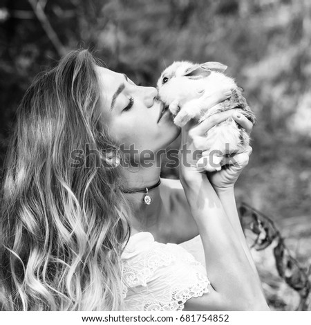 girl kisses cute little rabbit on summer day on natural background, black and white