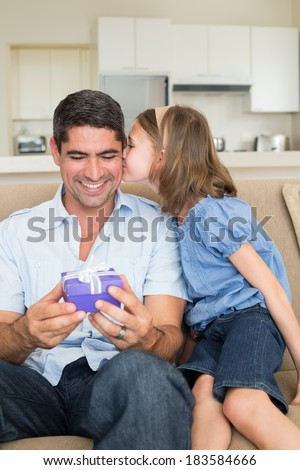 Girl kissing father holding gift box while sitting on sofa at home - stock photo