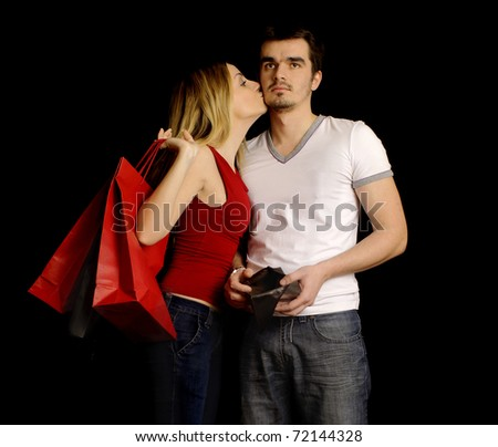 Girl kissing her boyfriend for buying her presents, boyfriend is showing his empty wallet