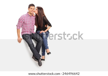 Girl kissing her boyfriend seated on a panel isolated on white background - stock photo