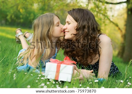 Girl kissing her mother and holding the gift box - stock photo