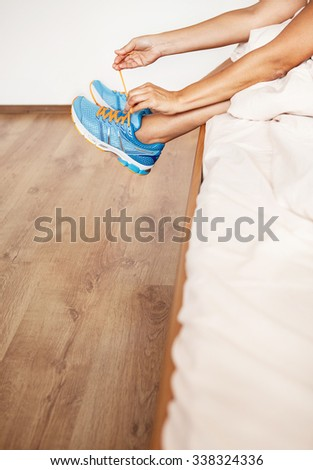 Girl lace her run shoes sitting in bed at the morning - stock photo