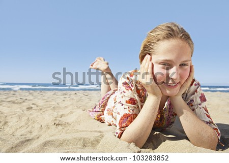 Girl laying down on a golden sand beach, smiling at the camera and wearing a floral dress. - stock photo