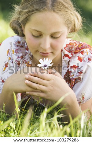 Girl laying down on green grass, smelling a daisy flower and smiling. - stock photo
