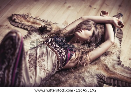 Girl laying on a skin of the wolf - stock photo