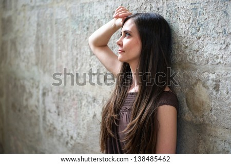 Girl leaning against a wall - stock photo