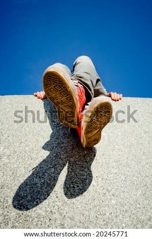 Girl legs in red sneakers against blue sky - stock photo