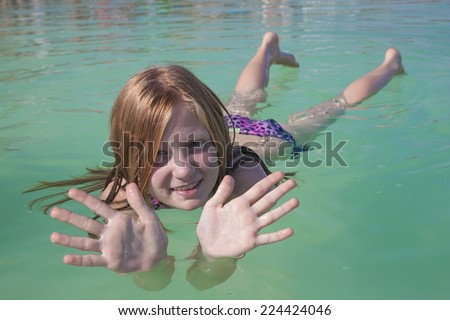 Girl lies on the water in the Dead Sea. The high concentration of salt in the water - keeps the body on the water surface - stock photo