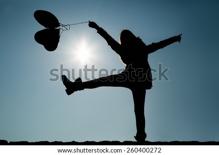 Girl lifting leg and arms in the air while holding balloons - stock photo