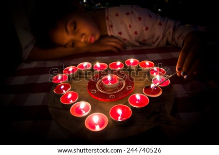 girl lights the candles that form the heart of love for Valentine's Day - stock photo